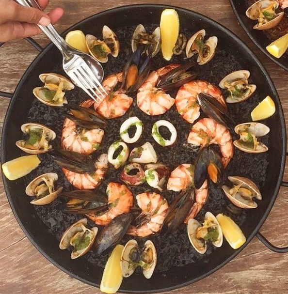 Our Arroz Negro de Mariscos which is a Paella dish with traditional seafood rice using squid ink and is also one of Carlos' preferred dishes from the menu